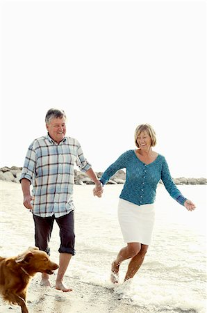 Happy couple with dog enjoying at beach Stock Photo - Premium Royalty-Free, Code: 698-06444455