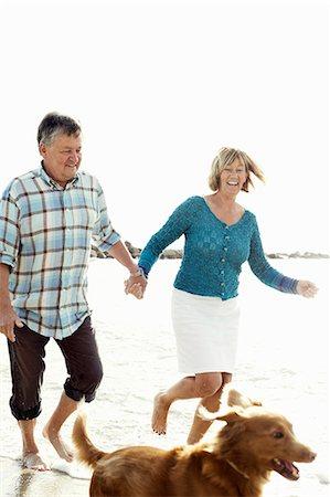 Happy couple running behind dog at beach Stock Photo - Premium Royalty-Free, Code: 698-06444456