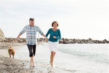 Dog chasing couple at beach Stock Photo - Premium Royalty-Free, Code: 698-06444457