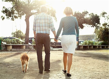 Rear view of couple walking with dog in park Stock Photo - Premium Royalty-Free, Code: 698-06444450