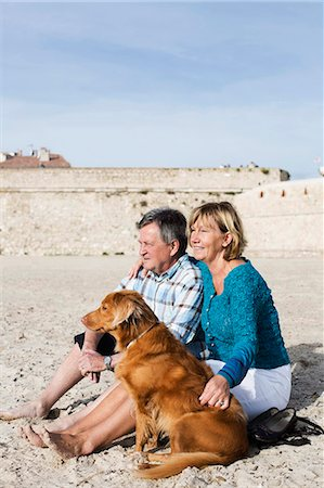 Couple with dog sitting on sand at beach Stock Photo - Premium Royalty-Free, Code: 698-06444461