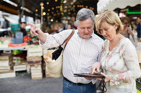 Couple using digital tablet while standing against market Stock Photo - Premium Royalty-Free, Code: 698-06444484