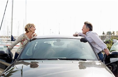 Side view of couple looking at each other while leaning on car Stock Photo - Premium Royalty-Free, Code: 698-06444489