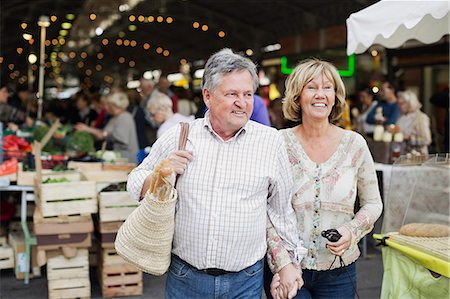 Happy couple looking away with market in the background Stock Photo - Premium Royalty-Free, Code: 698-06444482