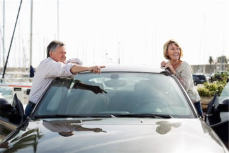 Senior man showing something to woman while leaning on car Stock Photo - Premium Royalty-Free, Code: 698-06444490