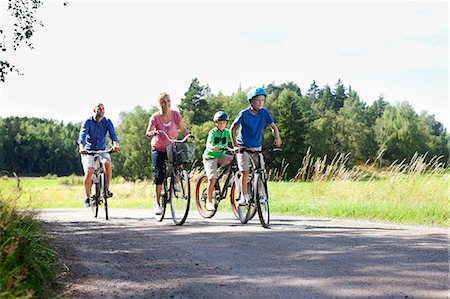 Caucasian family riding bicycles on country road during vacations Stock Photo - Premium Royalty-Free, Code: 698-06444503