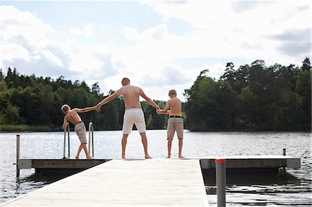 father son bath - Rear view of pre-adolescent boys standing with father at the edge of boardwalk Stock Photo - Premium Royalty-Free, Code: 698-06444516