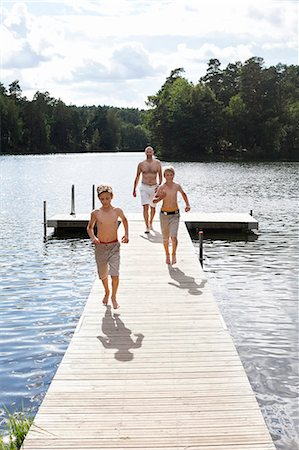 father son bath - Pre-adolescent boys running on boardwalk with father walking behind Stock Photo - Premium Royalty-Free, Code: 698-06444517