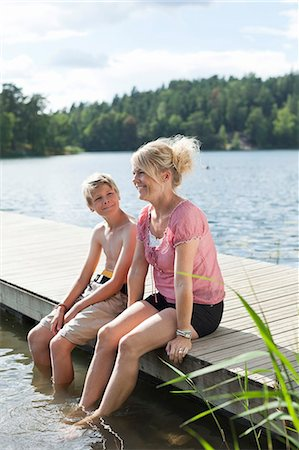Happy mature woman sitting with son on pier during vacations Stock Photo - Premium Royalty-Free, Code: 698-06444519