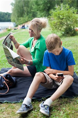 Mature woman reading newspaper sitting with son using cell phone at park Stock Photo - Premium Royalty-Free, Code: 698-06444513