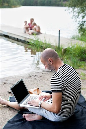 father son bath - Mature man using laptop at beach with family sitting on pier Stock Photo - Premium Royalty-Free, Code: 698-06444524