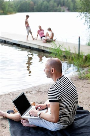 father son bath - Mature man looking away while using laptop at beach with family sitting on pier Stock Photo - Premium Royalty-Free, Code: 698-06444525