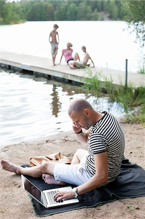 father son bath - Mature man using laptop while communicating on cell phone at beach with family sitting on pier Stock Photo - Premium Royalty-Free, Code: 698-06444526
