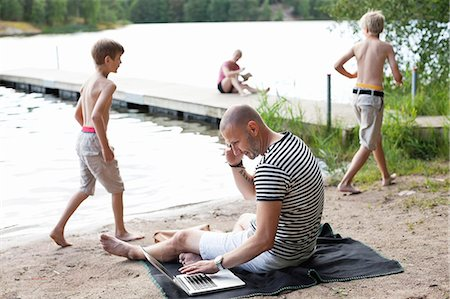 father son bath - Mature man using laptop while communicating on cell phone at beach with family in the background Stock Photo - Premium Royalty-Free, Code: 698-06444527