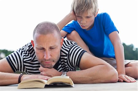 father son bath - Mature man reading book while lying on pier with son sitting behind Stock Photo - Premium Royalty-Free, Code: 698-06444529