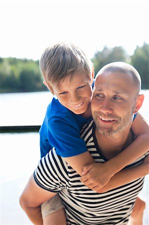 father son bath - Happy mature man giving his son a piggyback ride at beach Stock Photo - Premium Royalty-Free, Code: 698-06444531