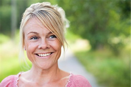 Close-up of happy mature woman looking sideways Stock Photo - Premium Royalty-Free, Code: 698-06444542