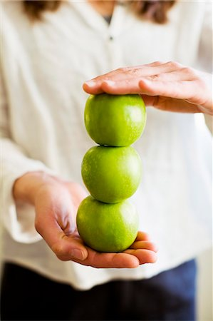 Midsection of woman holding stack three fresh granny smith apples Stock Photo - Premium Royalty-Free, Code: 698-06443730