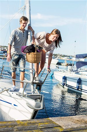 Young couple getting out from sail boat Stock Photo - Premium Royalty-Free, Code: 698-06443744
