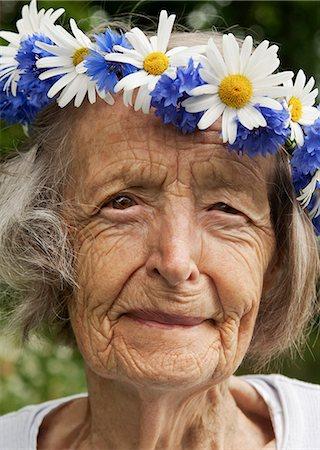 Portrait of senior woman wearing wreath of flowers on her head Stock Photo - Premium Royalty-Free, Code: 698-06443897