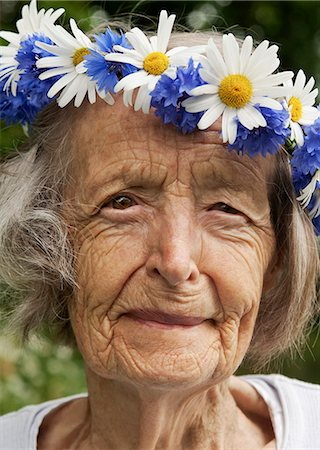 Portrait of senior woman wearing wreath of flowers on her head Stock Photo - Premium Royalty-Free, Code: 698-06443897