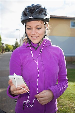 Happy woman in cycling helmet listening to music through cell phone Stock Photo - Premium Royalty-Free, Code: 698-06443936