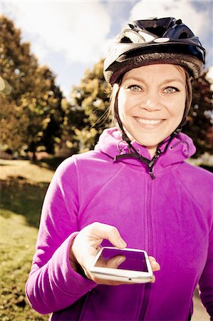 showing - Portrait of happy female cyclist holding smart phone outdoors Stock Photo - Premium Royalty-Free, Code: 698-06443940