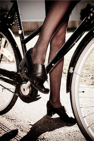 stocking feet - Low section of businesswoman in stockings standing with bicycle Stock Photo - Premium Royalty-Free, Code: 698-06443953