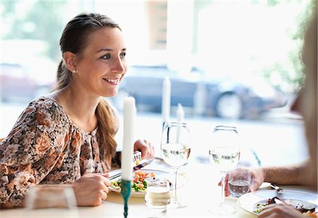 friendship - Happy young woman looking at friend at restaurant table Stock Photo - Premium Royalty-Free, Code: 698-06443960