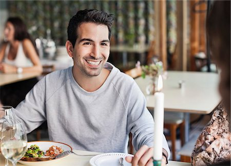 people eating at lunch - Happy man looking at female friend at restaurant table with people in the background Stock Photo - Premium Royalty-Free, Code: 698-06443961