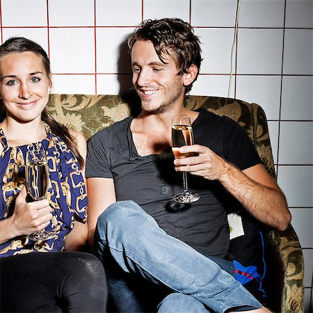 saloon - Couple holding champagne flutes on sofa at saloon Stock Photo - Premium Royalty-Free, Code: 698-06443986