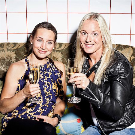 saloon - Portrait of happy female friends holding champagne flutes on sofa Stock Photo - Premium Royalty-Free, Code: 698-06443988
