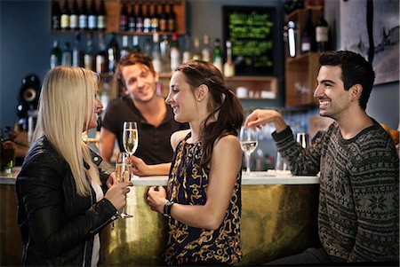 Side view of friends smiling while bar tender looking at them Stock Photo - Premium Royalty-Free, Code: 698-06443990