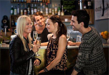 saloon - Bar tender looking at friends smiling at counter Stock Photo - Premium Royalty-Free, Code: 698-06443991
