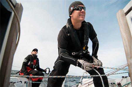 sailboat  ocean - Man tying rope while woman sitting behind in sailboat Stock Photo - Premium Royalty-Free, Code: 698-06615394