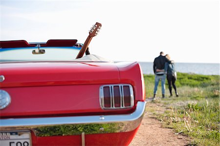 Close-up of red car with couple in background on field Stock Photo - Premium Royalty-Free, Code: 698-06615486