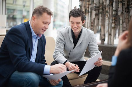 partnership - Happy businessmen going through paperwork in office Stock Photo - Premium Royalty-Free, Code: 698-06615514