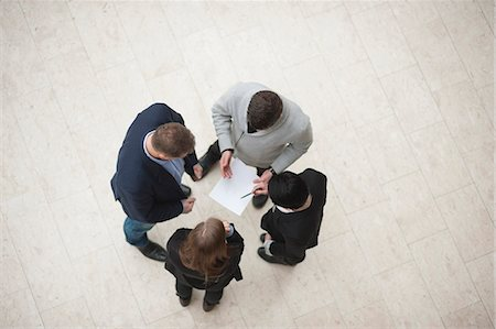 Directly above shot of four businesspeople in meeting Stock Photo - Premium Royalty-Free, Code: 698-06615519