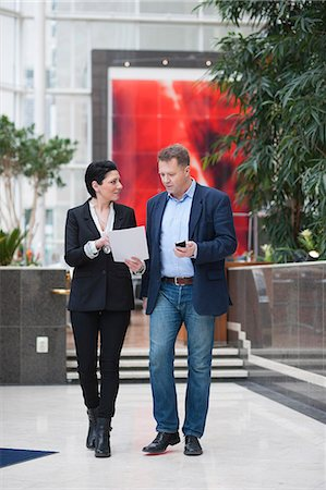 Full length of businessman with female colleague discussing paperwork while walking in office Stock Photo - Premium Royalty-Free, Code: 698-06615513