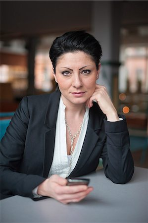 short hair - Portrait of serious businesswoman holding mobile phone sitting at table Stock Photo - Premium Royalty-Free, Code: 698-06615528