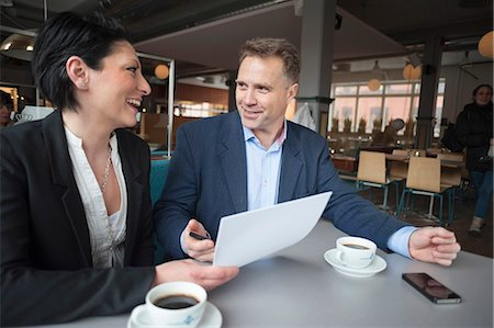 event - Mature businessman with female colleague discussing paperwork in cafe Stock Photo - Premium Royalty-Free, Code: 698-06615529