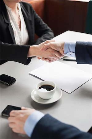Businesspeople shaking hands over restaurant table Stock Photo - Premium Royalty-Free, Code: 698-06615535