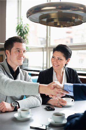 Business people shaking hands in a cafe meeting Stock Photo - Premium Royalty-Free, Code: 698-06615537