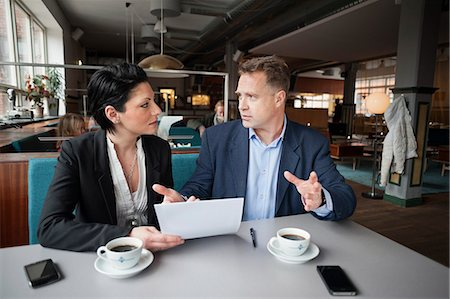 Mature businessman and female colleague with paperwork at cafe table Stock Photo - Premium Royalty-Free, Code: 698-06615530