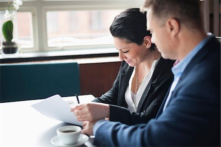 Businessman looking at woman signing contract in cafe Stock Photo - Premium Royalty-Free, Code: 698-06615531