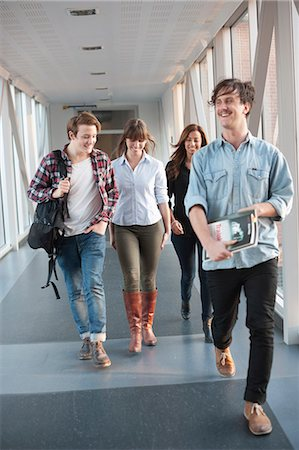 Happy young university student walking in corridor Stock Photo - Premium Royalty-Free, Code: 698-06615598