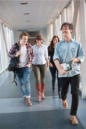 Happy young university student walking in corridor Stock Photo - Premium Royalty-Free, Code: 698-06615598