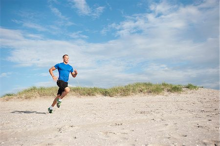 Full length of young man jogging on sandy beach over cloudy sky Stock Photo - Premium Royalty-Free, Code: 698-06615607