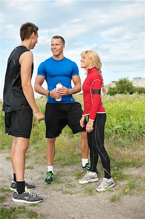 Three friends having break from exercising in field Stock Photo - Premium Royalty-Free, Code: 698-06615613