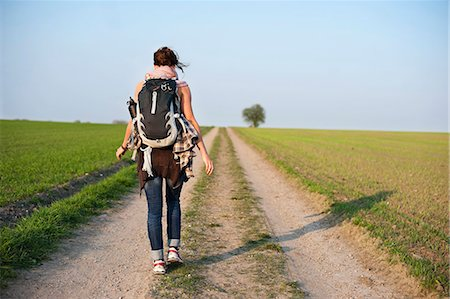 Rear view of young woman with backpack on a hiking trail Stock Photo - Premium Royalty-Free, Code: 698-06615637